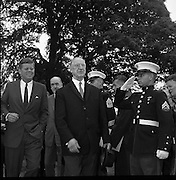 U.S. President John F. Kennedy  exits the U.S. Embassy to board a helicopter to take him to London to meet Mr. Harold MacMillan. He is accompanied by President Éamon de Valera.