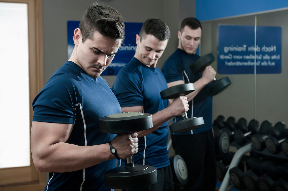 Three young men doing weight training in gym