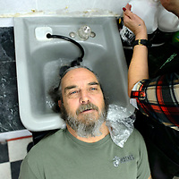 Grants mayor Modie Hicks soaks for a wash by stylist Clorinda Brito at Clo's Hair Design in Grants Thursday. Hicks had his hair cut after a fundraiser to benefit the Marine ROTC drill team trip to a national competition.