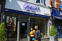 © Licensed to London News Pictures. 24/04/2020. London, UK. A woman wearing a face mask walks past a closed hairdresser in north London. According to government officials, hairdressers could be forced to remain closed for six more months to reduce the risk of the spread of COVID-19. Photo credit: Dinendra Haria/LNP
