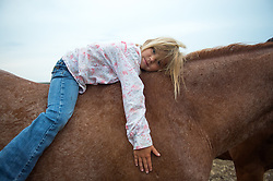 "The Nature Conservancy's Matador Ranch Operations Manager Charlie Messerly's daughter Layla sits on her horse in Eastern Montana  at the Matador ranch ""grass bank"". The ""grass bank"" is an innovative way to leverage conservation gains, in which ranchers can graze their cattle at discounted rates on Conservancy land in exchange for improving conservation practices on their own ""home"" ranches. In 2002, the <br /> Conservancy began leasing parts of the ranch to neighboring ranchers who were suffering from  severe drought, offering the Matador's grass to neighboring ranches in exchange for their  participation in conservation efforts. The grassbank has helped keep ranchers from plowing up native grassland to farm it; helped remove obstacles to pronghorn antelope migration; improved habitat for the Greater Sage-Grouse and reduced the risk of Sage-Grouse colliding with fences; preserved prairie dog towns and prevented the spread of noxious weeds. (Photo By Ami Vitale)"