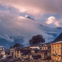 Lukla village in the Khumbu Region of Nepal glows in the sunset, under a Himalayan summit.