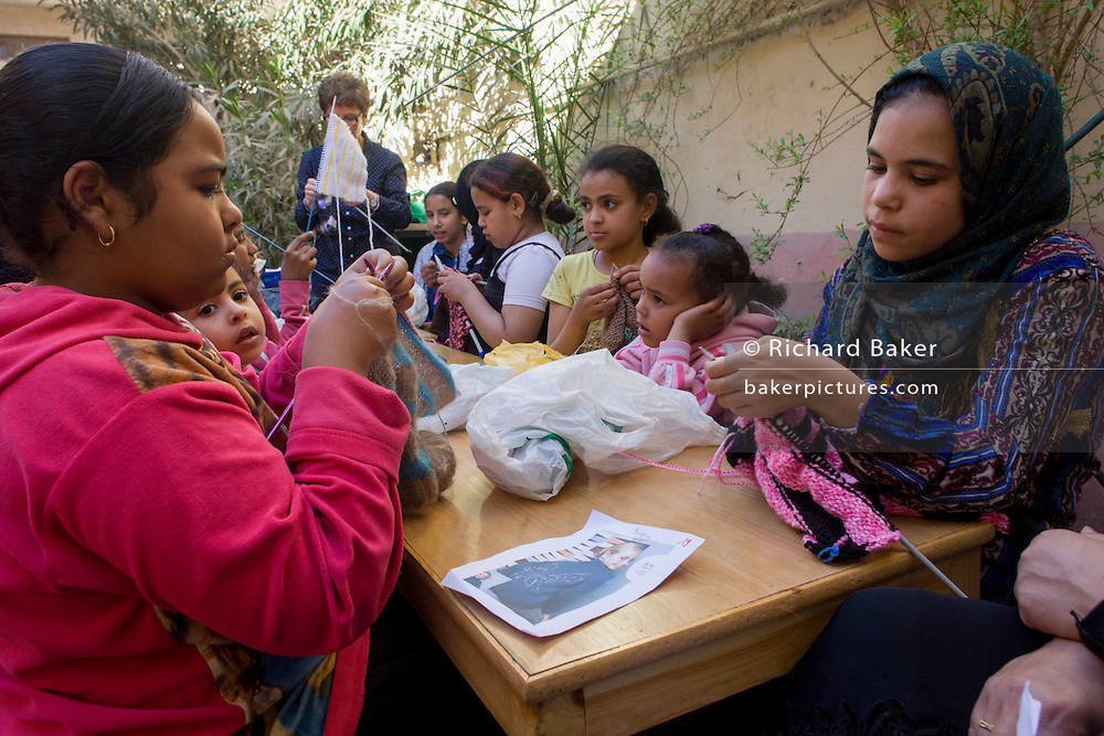 Young Egyptian girls learn to knit with the help of Belgian teaching volunteers at the American-sponsored Theban Mapping Project Library on the West Bank of Luxor, Nile Valley, Egypt. The Theban Mapping Project's goal is to enable local people to have a place where they can read and learn. The organisation is run by American Egyptologist Dr Kent Weeks who is committed to the original goal of accurately documenting the archaeological heritage of Thebes