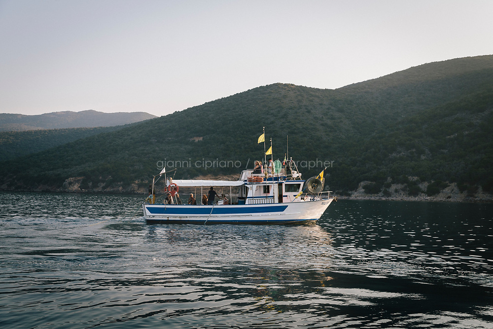 """TALAMONE, ITALY - 27 AUGUST 2019: Fisherman and activist Paolo Fanciulli's """"Sirena"""" fishing boat is seen here in Talamone, Italy, on August 27th 2019.<br /> <br /> In 2006, fisherman Paolo Fanciulli used government funds and the donations from his loyal excursion clients to fund a project in which they protected the local waters from trawling by dropping hundreds of concrete blocks around the seabed. But his true dream was to lay down works of art down on the sea floor off the coast of Tuscany. His underwater art dreams came true when the owner of a Carrara quarry, inspired by Mr. Fanciulli's vision, donated a hundred marble blocks to the project.<br /> Mr. Fanciulli invited sculptors to work the marble and set up kickstarter accounts, boat tours and dinners to fund the project. The acclaimed British artist Emily Young carved a ten-ton """"Weeping Guardian"""" face, which was lowered with other sculptures into the water in 2015.<br /> Since then, coral and plant life have covered the sculptures and helped bring back the fish. And Paolo the Fisherman is catching as many of them as he can."""