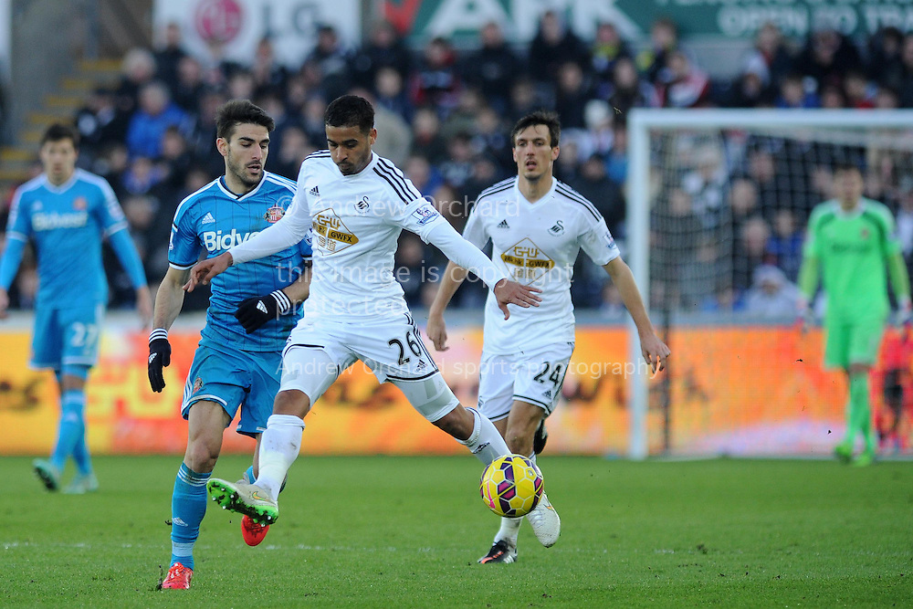Kyle Naughton of Swansea city gets in to stop Jordi Gomez of Sunderland. Barclays premier league match, Swansea city v Sunderland at the Liberty stadium in Swansea, South Wales on Saturday 7th Feb 2015.<br /> pic by Andrew Orchard, Andrew Orchard sports photography.