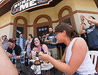 Reuben Bassett keeps the timer while Lillia Grablewsky and Kelly Carter tackle their burritos during their annual burrito eating contest at Burrito Me on Thursday afternoon.  (Karen Bobotas/for the Laconia Daily Sun)
