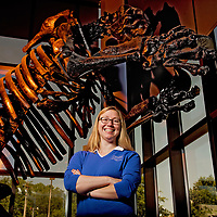 Amy Thorton, Cape Fear Museum Education Manager stands beneath a replica of giant sloth in the lobby of the museum.