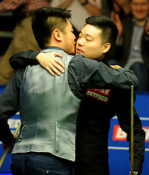 Ding Junhui (right) is congratulated by Liang Wenbo after winning 13-12 frames on day eight of the Betfred Snooker World Championships at the Crucible Theatre, Sheffield.