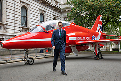 © Licensed to London News Pictures. 23/05/2018. London, UK. Defence Secretary Gavin Williamson stands in front of a Royal Air Force (RAF) Red Arrow jet on Downing Street as part of the RAF100 Centenary celebrations. Photo credit: Rob Pinney/LNP