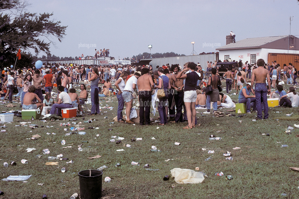 Folks going into The Grateful Dead Concert at Raceway Park, Englishtown NJ on 3 September 1977. Labor Day Weekend and on The Road into the Show. This shot taken outside the venue leading up to a gate which you can see here just to the left of center next to the Good Humor stand.