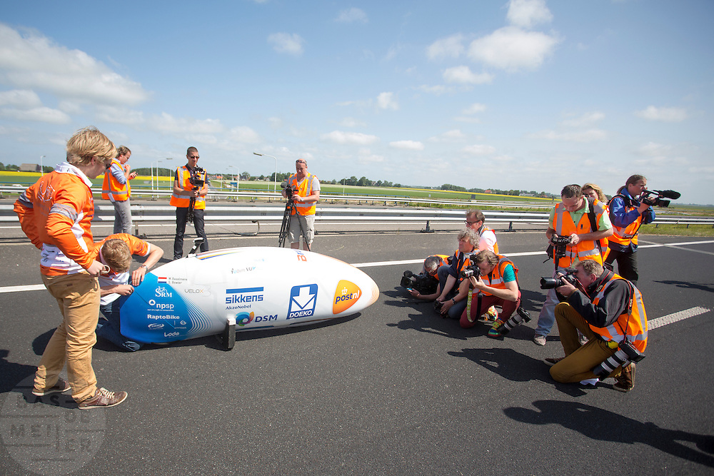 Fotografen maken een foto van de VeloX3. Het Human Power Team Delft en Amsterdam presenteert de nieuwe fiets, de VeloX3, in Friesland. Fietser Sebastiaan Bowier rijdt met de VeloX3 over de A31 tussen Franeker en Donrijp. Het team hoopte op een snelheid van boven de 80 km/h, maar door de harde zijwind komt Bowier niet verder dan 78,8 km/h. Met de speciale ligfiets wil het team dat bestaat uit studenten van de TU Delft en de VU Amsterdam het wereldrecord fietsen verbreken. Dat staat nu op 133 km/h.<br /> <br /> Photographers take pictures of the VeloX3. The Human Power Team Delft and Amsterdam presents their new record bike, the VeloX3, in Friesland. Cyclist Sebastiaan Bowier cycles with the VeloX3 on the A31 highway between Franeker and Donrijp. They hoped to get above the 80 km/h, but due to the severe side winds Bowier reaches 78,8 km/h maximum.  With the special recumbent bike the team, consisting of students of the TU Delft and the VU Amsterdam, wants to set a new world record cycling. The current speed record is 133 km/h.