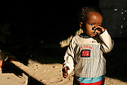 Bakar, 2, is crying at dawn in front of his home  in the unrecognised village of Wadi el Na'am, pop. 4000, close to Beer Sheva, the capital of the Negev, a large deserted area in the south of Israel.  Wadi el Na'am is located near a large industrial site, Ramat Hovav, and has no infrastructure or electric energy. Water is provided only via storage tanks. It has no health services as the only clinic is deemed illegal and bound to be demolished, as the rest of the structures in the area. Numbering around 200.000 in Israel, the Bedouins constitute the native ethnic group of these areas, they farm, grow wheat, olives and live in complete self sufficiency. Many of them were in these lands long before the Israeli State was created and their traditional lifestyle is now threatened by subtle Governmental policies. The seven Bedouin towns already built are all between the 10 more impoverished towns in Israel. ..