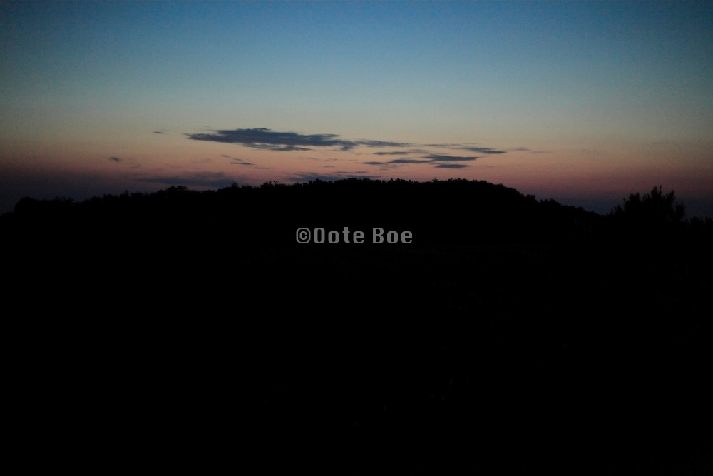 dramatic sunrise against a hilly silhouette