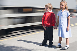 Innocent children walking along the pavement with busy urban traffic in the background conveying the message that the future wellbeing of our children is under threat unless there is a reduction in carbon emissions,