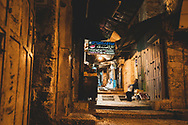 Jerusalem - October 19, 2010: A Palestinian shopkeeper sits outside his shop at night on Chain Street in the Muslim Quarter of Jerusalem's Old City