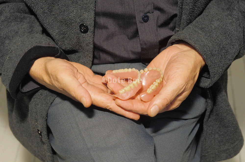 a man holding his artificial teeth