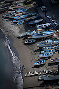 A fisherman brings a net up on shore as a docked fishing fleet of boats covers the beach, Sorrento Harbor, Campania, Italy. Original, untreated image available upon request.
