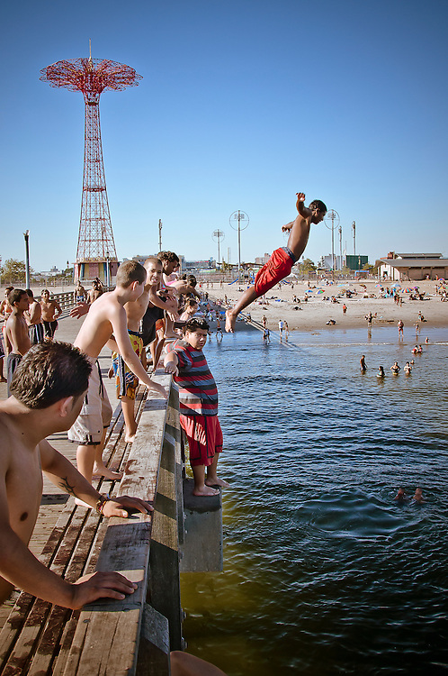 A kid dives in the water from the Coney island pier in Brooklyn, New York, 2010.