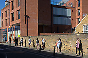 As the second week of the UK governments Coronavirus lockdown ends on a fine Spring weekend, a queue of Londoners stand outside a Tesco Express in Herne Hill, on 5th April 2020, in London, England.