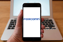 Using iPhone smartphone to display logo of Foxconn (Technology), Taiwanese multinational electronics contract manufacturing company