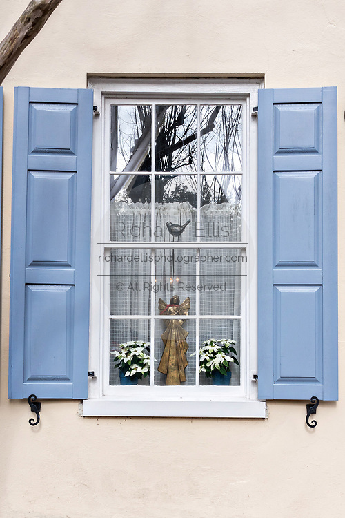 Christmas decorations in the window of a historic home decorated with blue shutters on Tradd Street in Charleston, SC.
