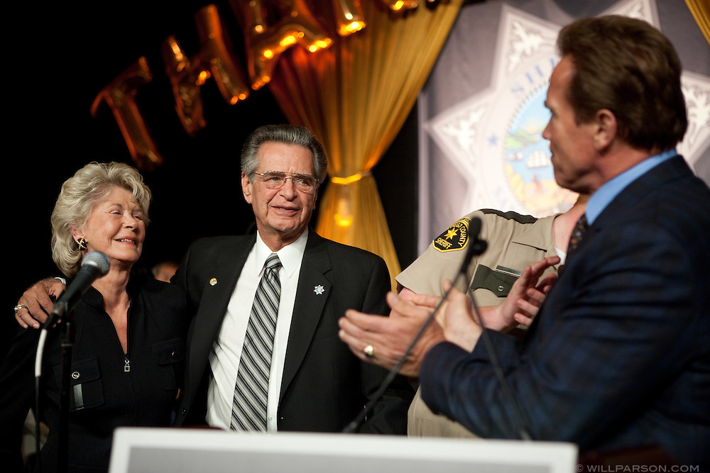 """California Governor Arnold Schwarzenegger speaks at the retirement party honoring San Diego Sheriff Bill Kolender, Oct. 05, 2009. Kolender stands with his wife Lois. At one point Schwarzenegger pinched Kolender's cheek and joked, """"He did the security for Moses."""""""