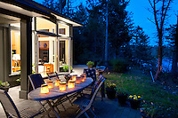 A home with large glowing windows is set in a forested hillside overlooking a BC Ferries water route.