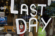 The words 'Last Day' are painted in white emulsion on a window Camden North London, England. A Jesus figure, dolls  and various bric a brac are seen in the window behind the large lettering. Around a recession-bled Britain, high-street businesses have been going bust in their thousands. Britain has now endured eight recessions since the Second World War. No two recessions are alike, and that applies to the current slowdown also. It has been caused by a shock to the availability of credit, a massive build up of debt. The number of people out of work currently stands at almost two million. Given the rate at which the economy is deteriorating this could easily be above three million. From a continuing piece of work about windows and urban messages, the picture is from the project of closed business windows: 'Bust - the Art of Recession'.
