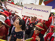 April 6, 2014 - Bangkok, Bangkok, Thailand - <br /> <br /> Red Shirts Rally in Bangkok Suburbs<br /> <br /> Red Shirts supporters at a pro government rally hold up signs protesting the Thai courts and military who they suspect of harboring anti-government factions. Red Shirts and supporters of the government of Yingluck Shinawatra, the Prime Minister of Thailand, gathered in a suburb of Bangkok this weekend to show support for the government. The Thai government is dealing with ongoing protests led by anti-government activists. Legal challenges filed by critics of the government could bring the government down as soon as the end of April. The Red Shirt rally this weekend was to show support for the government, which public opinion polls show still has the support of most of the electorate. <br /> ©Exclusivepix