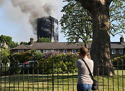 A man photographs a fire that has engulfed the 27-storey Grenfell Tower in west London.