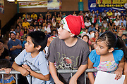 July 13, 2008 -- PHOENIX, AZ: Children wait for their favorite Luchadors (wrestlers) during a Lucha Libre show at El Gran Mercado in Phoenix. Lucha Libre is Mexican style wrestling. There are heros (Tecnicos) and villians (Rudos). The masks are popular as children's gifts and tourist mementos. As the size of the Mexican community in the Phoenix area has grown, attendance at the Lucha Libre shows has increased. Lucha Libre differs from American style entertainment wrestling in several ways, but principally the wrestlers are more acrobatic and rely less on body slams than American wrestling. The shows, which used to be held only periodically, are now held every week at El Gran Mercado, a flea market and swap meet that caters mostly to the Mexican community in Phoenix.   Photo by Jack Kurtz / ZUMA Press