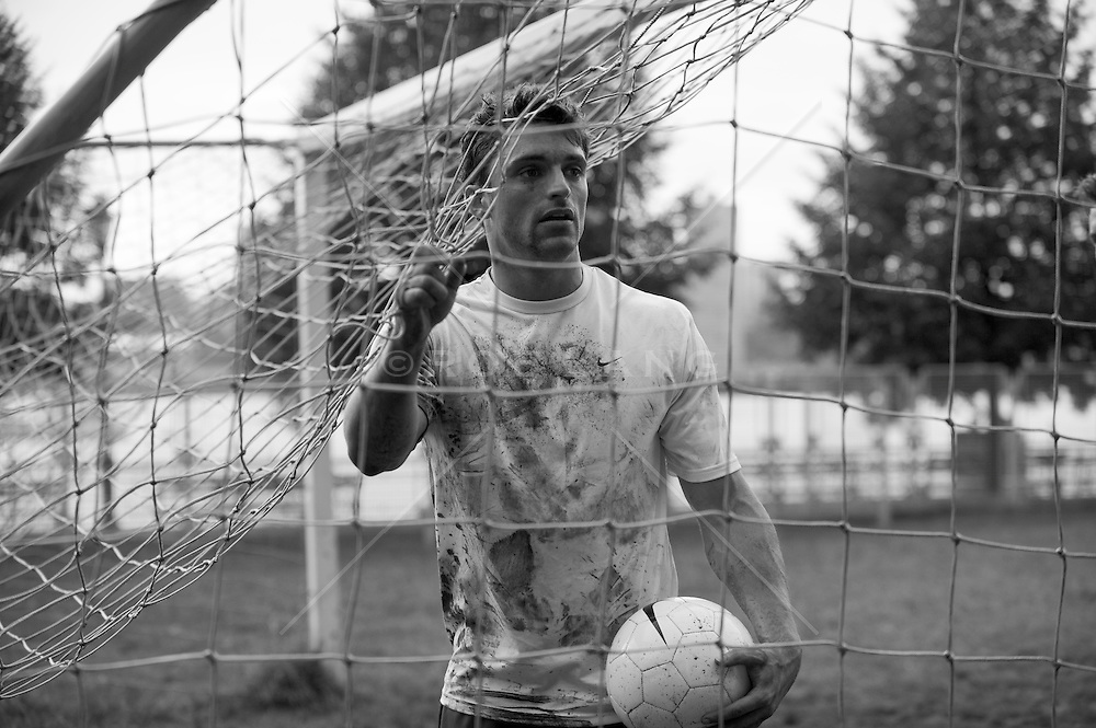 Man covered in mud holding a soccer ball under the field goal net