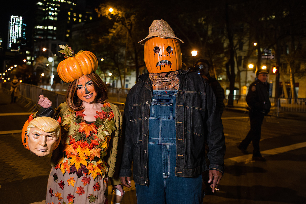 """New York, NY - 31 October 2016. A couple dressed as scarecrows with pumpkin heads carry a Halloween treat bucket in the shape of a pumpkin with a mask of Donald Trump on the front, and lettered """"Jerk o' [lantern]"""""""