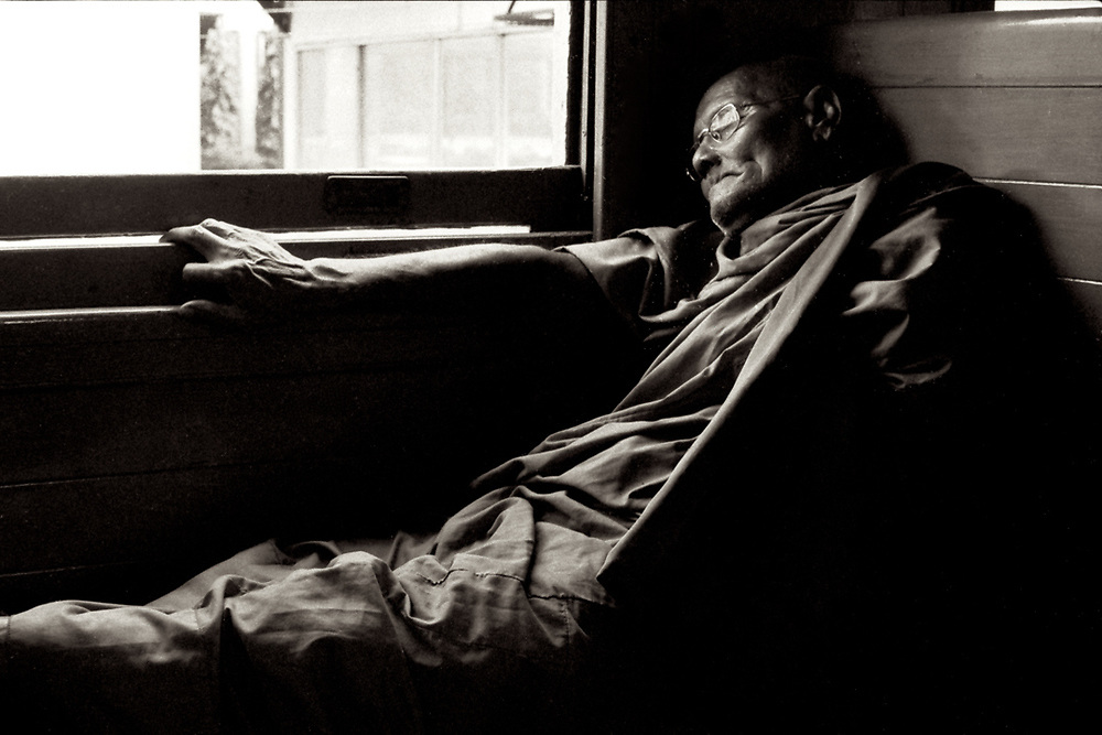 A Buddhist Monk sleeping on the train to Chiang Mai, Thailand. Photo by Lorenz Berna
