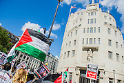 """Outside the BBC a huge flag is unfurled and as the march heads off peace signs alternate with pointing and chanting - Shame on you. Stop the 'massacre' in Gaza protest. A demonstration called by the Palestine Solidarity Campaign (PSC). They assembled at the BBC offices in Regent Street and marched to The US Embassy and on to a rally in Hyde Park. They called for """"Israel's bombing and killing to stop now and for David Cameron to stop supporting Israeli war crimes"""". London, 09 Aug 2014."""