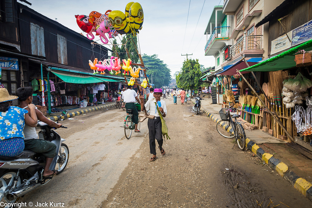 06 JUNE 2014 - IRRAWADDY DELTA,  AYEYARWADY REGION, MYANMAR: An inflatable toy vendor walks down the street in Pantanaw, a town in the Irrawaddy Delta (or Ayeyarwady Delta) in Myanmar. The region is Myanmar's largest rice producer, so its infrastructure of road transportation has been greatly developed during the 1990s and 2000s. Two thirds of the total arable land is under rice cultivation with a yield of about 2,000-2,500 kg per hectare. FIshing and aquaculture are also important economically. Because of the number of rivers and canals that crisscross the Delta, steamship service is widely available.   PHOTO BY JACK KURTZ