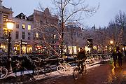 Een fietser rijdt in de schemer door een besneeuwd centrum van Utrecht.<br /> <br /> A cyclist is riding in a snowy Utrecht at twilight.