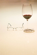 A glass of red wine and a pair of glasses against a white background The Dolly Irigoyen - famous chef and TV presenter - private restaurant, Buenos Aires Argentina, South America Espacio Dolli