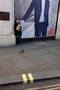 Man eats a sandwich beneath a poster for retailer H&M on Oxford Street.