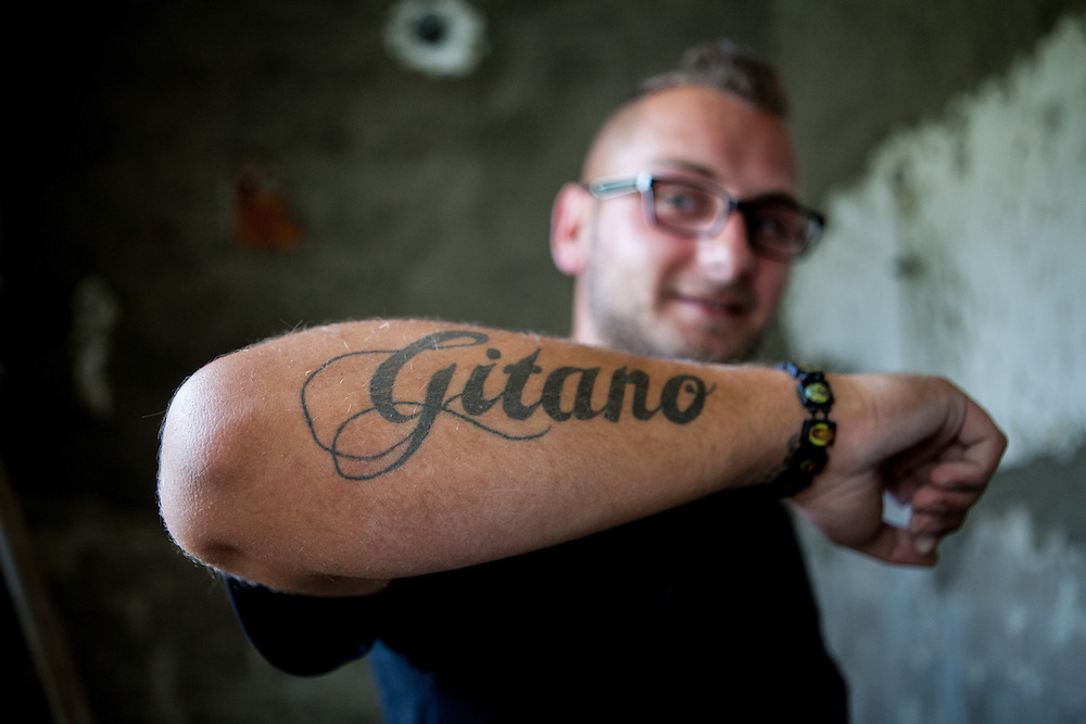 """A man with a """"Gitano"""" (Gypsy) tatoo in Rankovce working on the reconstruction of an old school building. The foundation ETP Slovakia has a project in setting up micro-loan funds for the local Roma community. Loans from this fund will enable families to build their own low-cost brick homes, on land they own."""