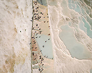 """Pamukkale, meaning """"cotton castle"""" in Turkish, is a natural site in Denizli. Dripping slowly down the vast mountainside, mineral-rich waters foam and collect in terraces, spilling over cascades of stalactites into milky pools below."""