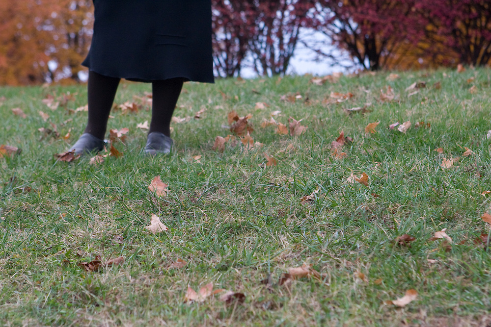 A woman clad in all black is seen from the knees down upon a green field strewn with autumn leaves.