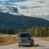 Heavy trucks drive below the Canadian Rockies on the Yellowtail Highway. Roche Miette bkg.