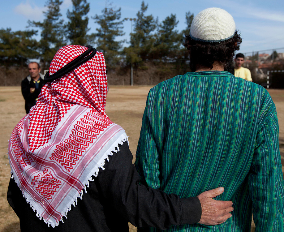 An unidentified Palestinian shiekh (L) hugs an unidentified Israeli Orthodox Rabbi at the conclusion of a friendly soccer match between Israelis and Palestinians, held at the Jewish settlement of Efrat in Gush Etzion, on January 28, 2010.