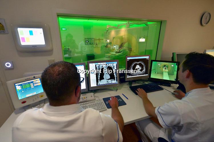 Nederland, Arnhem, 26-6-2017 Verschillende scanners van Philips Medical Systems in het ziekenhuis. Bijzonder zijn de CT scanner met Ambient Lighting. Een laborant maakt een ct scan van een patient die in de ct-scanner ligt. Foto: Flip Franssen