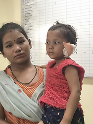 June 23, 2017 - NEW DELHI, INDIA - NEW DELHI, INDIA- JUNE, 22, 2017: Anju Devi, 19, (left) holding her injured three-year-old sister Beena, (right) whose ears were chopped off by her own father, pictured at a police station in New Delhi, India.....Amrit Bahadur, 35, beat his three-year-old daughter and chopped off both her ears, claiming that a supernatural power asked him to do so. He locked his wife and other children on the terrace and then tortured the girl.....Bahadur was arrested on the spot and is in police custody.....Pictures supplied by: Cover Asia Press (Credit Image: © Cover Asia Press/Cover Asia via ZUMA Press)
