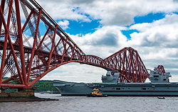 North Queensferry, Scotland, UK. 23 May 2019. Aircraft carrier HMS Queen Elizabeth sails from Rosyth in the River Forth after a visit to her home port for a refit. She returns to sea for Westlant 19 deployment and designed to focus on the operations of her F-35 fighter aircraft. Pictured; The Carrier passes below the Forth Bridge at low tide.