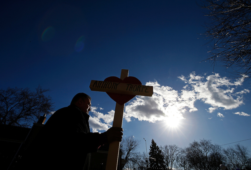 Leroy Vega carries a wooden cross in honor of shooting victim Anthony Thorpe at the site of a vigil for all the victims of violence since the start of the year in Chicago, Illinois.