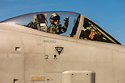 """A Thunderbolt A-10 pilot gives the """"hook 'em horns"""" gesture while readying for a mission.  Nellis AFB, Las Vegas, Nevada.  <br /> <br /> Created by aviation photographer John Slemp of Aerographs Aviation Photography. Clients include Goodyear Aviation Tires, Phillips 66 Aviation Fuels, Smithsonian Air & Space magazine, and The Lindbergh Foundation.  Specialising in high end commercial aviation photography and the supply of aviation stock photography for advertising, corporate, and editorial use."""