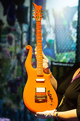 © Licensed to London News Pictures. 26/10/2017. London, UK. A curator holds an Orange Cloud guitar (2007) used by the musician Prince. This is the first ever exhibition about iconic superstar and legendary performer PRINCE showcases hundreds of never seen before artefact's directly from Paisley Park, Prince's famous Minnesota private estate. Photo credit: Ray Tang/LNP